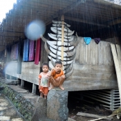Children Staying Dry in Primitive Village Flores